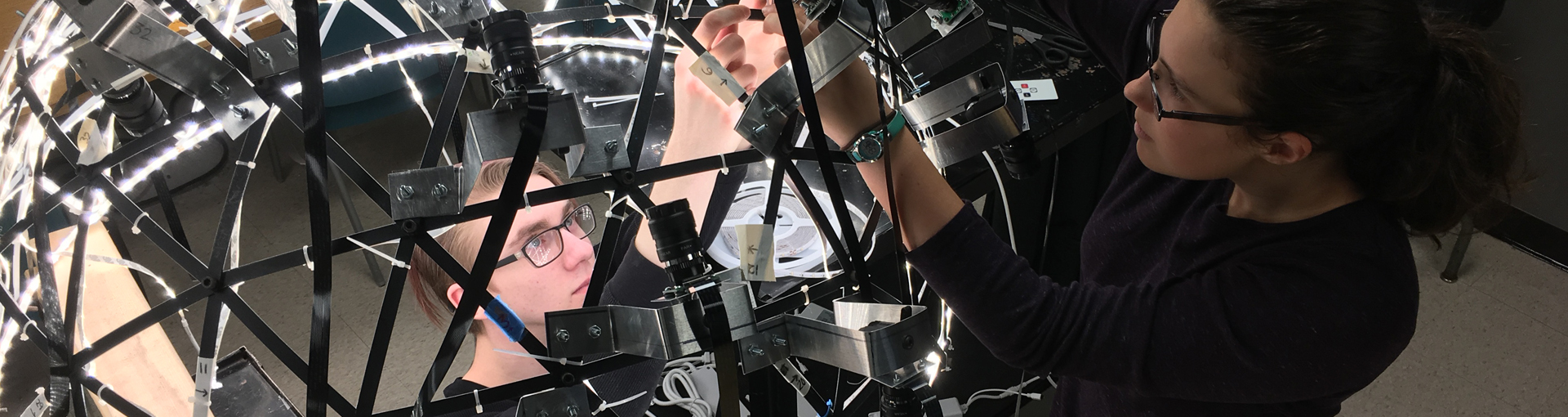 two female students working on dome-shaped imaging system