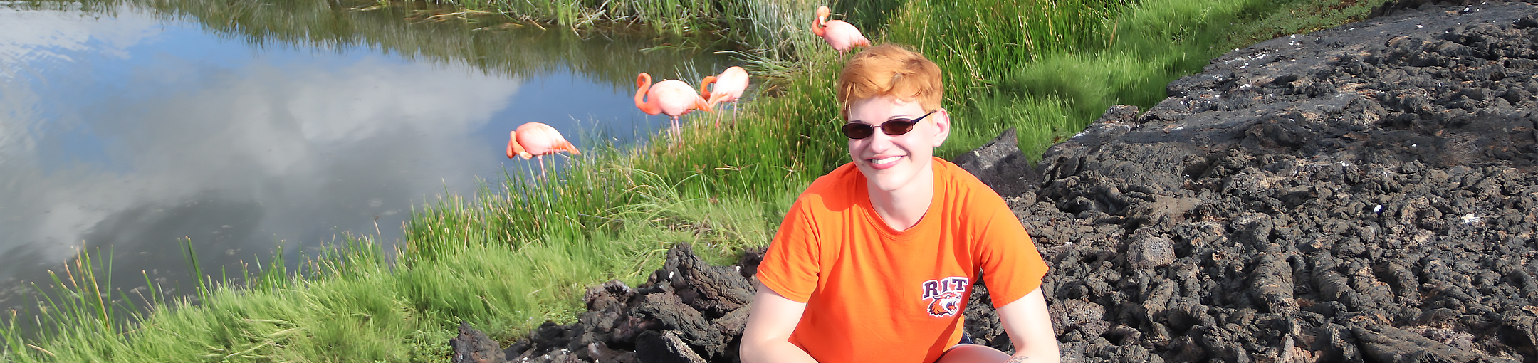 RIT student in front of flamingos in the Galapagos Islands