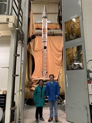 research student and faculty standing in front of a rocket