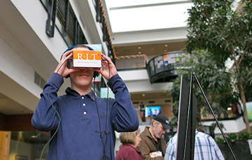 An attendee looks through an RIT-branded virtual reality device.