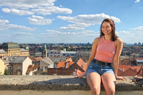 Lauren Kupferschmid sits in front of the Zagreb skyline