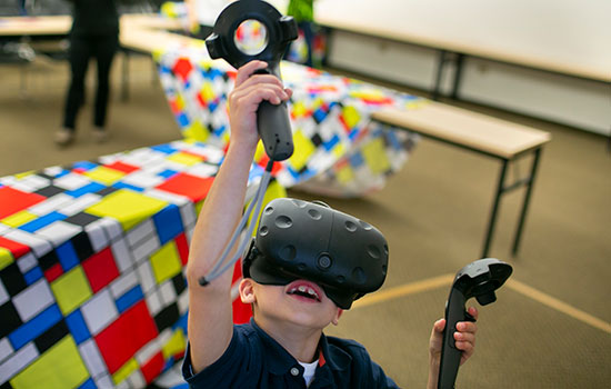 An young attendee uses virtual reality goggles and controllers.