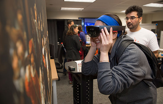 An attendee looks at a painting with augmented reality goggles.