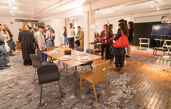 Attendees at the exhibit space, which includes a dining room table and chairs