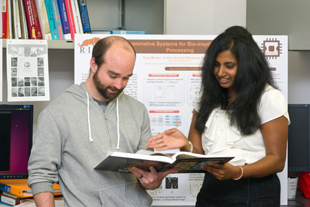 Kudithipudi and her doctoral student looking at a book