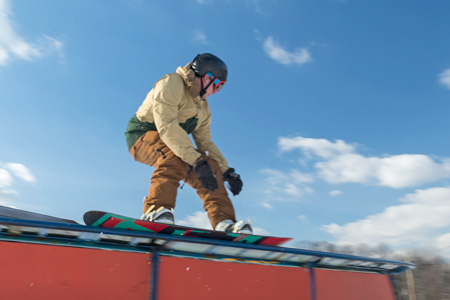A student on a snowboard slides along a rail during Rail Jam