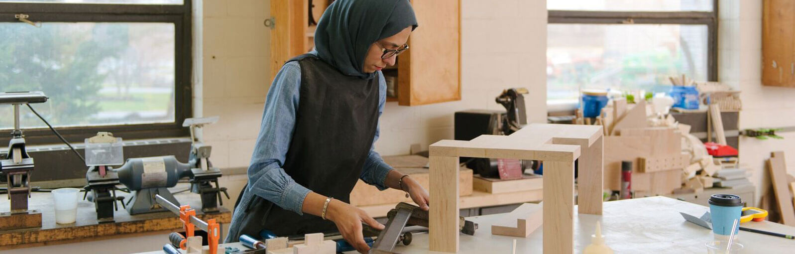 Student in a wood shop making something out of wood