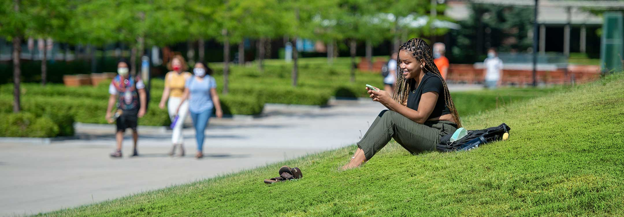 A student sitting in the grass at RIT.