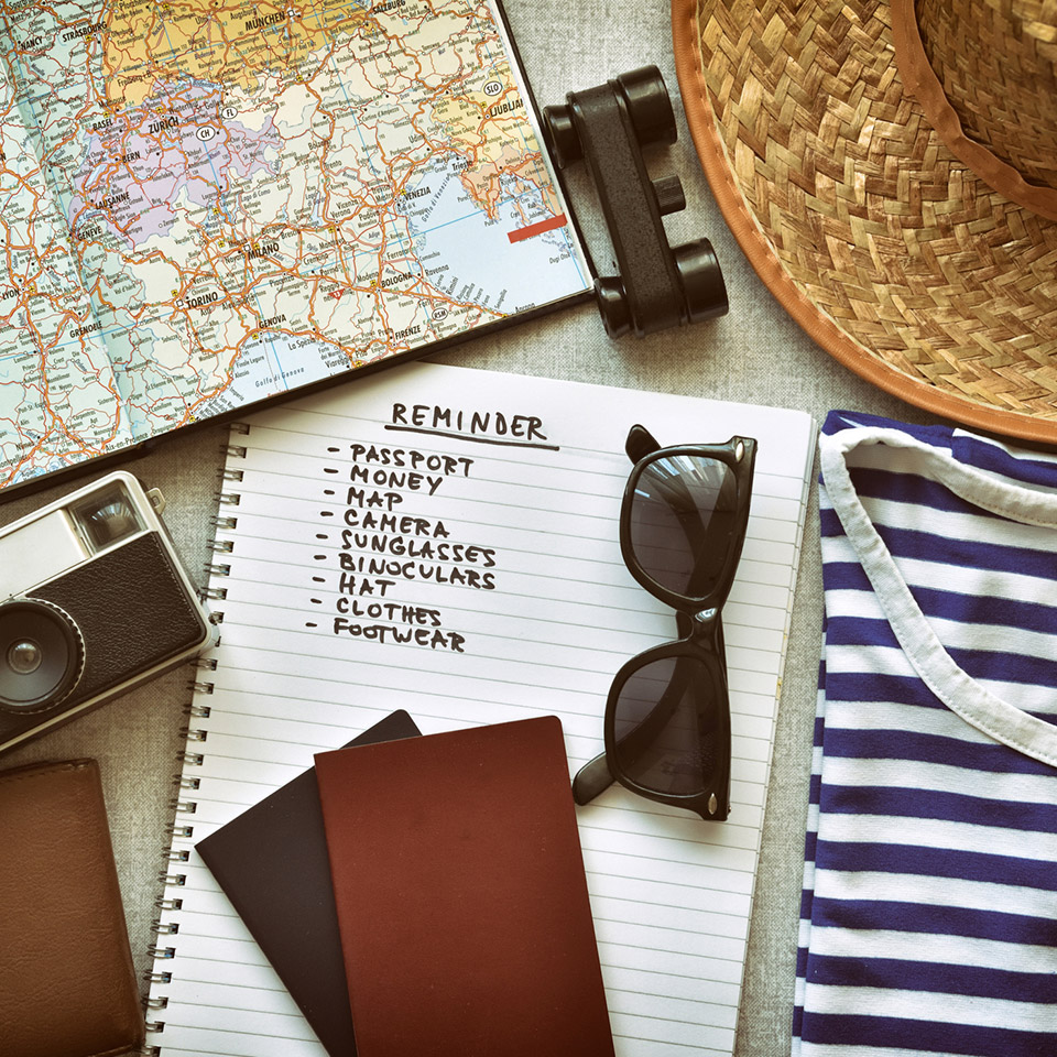 Top-down view of vacation items like sunglasses, a map, and passports