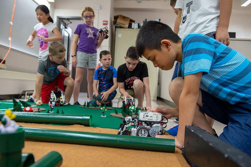 Elementary-school students place toy robots on maze.