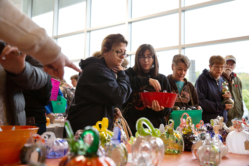 People shopping for glass pumpkins