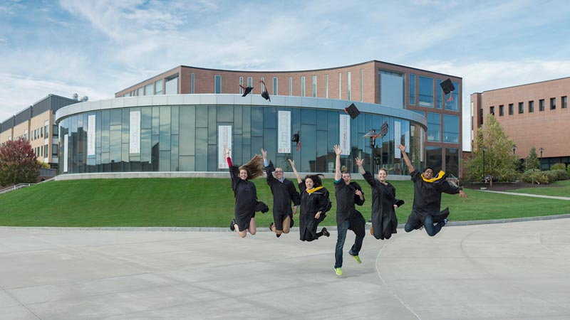 Students all jumping at once in front of a building