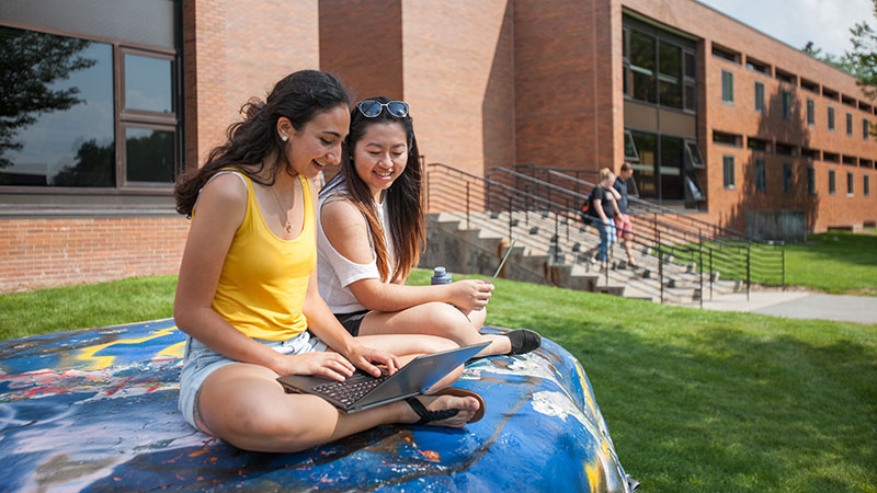 students outside sitting on a painted rock