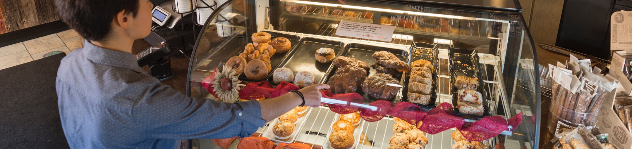 A person pointing to a baked good in a display case at the Artesano Bakery and Cafe.