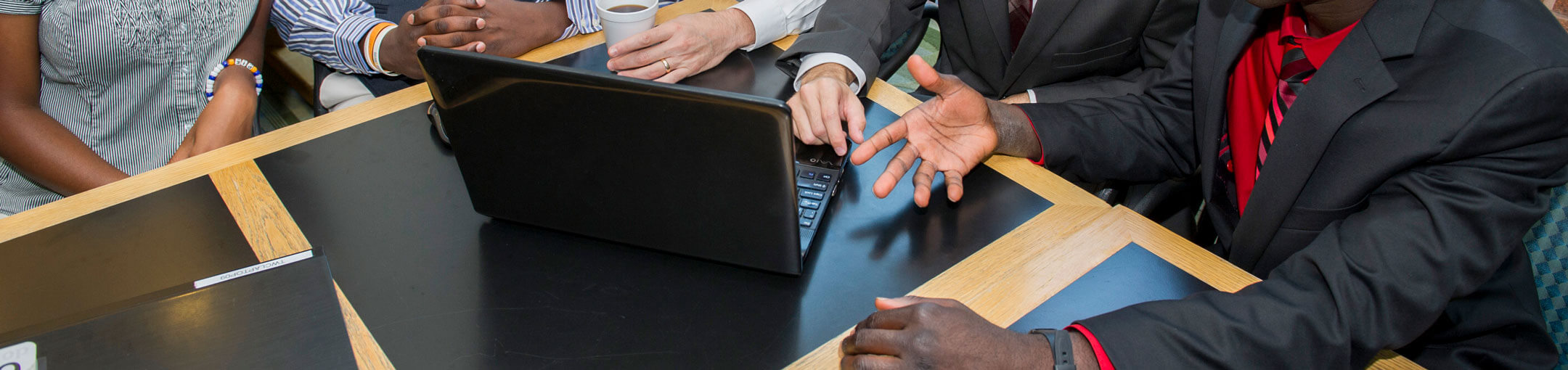 five people around a laptop discussing something in a meeting