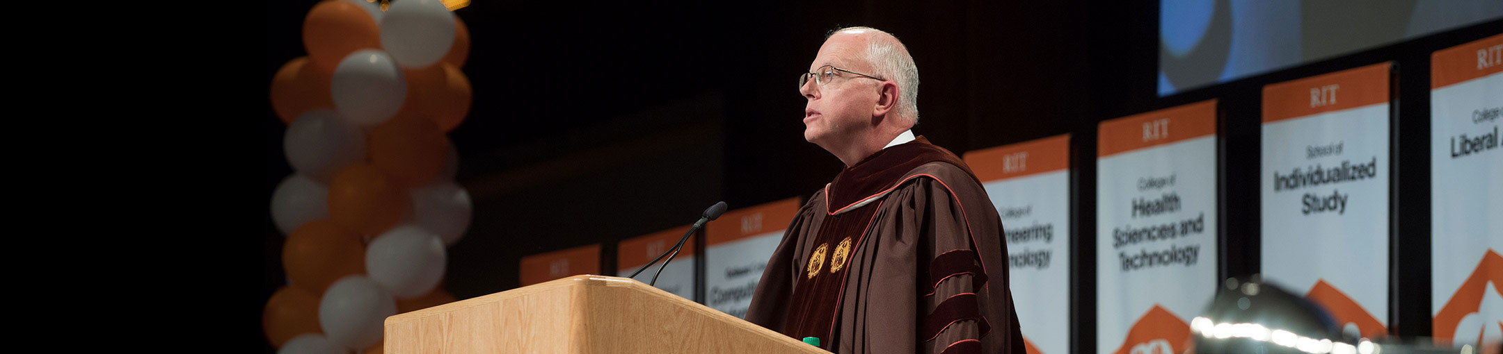President Munson addressing a group at a graduation ceremony