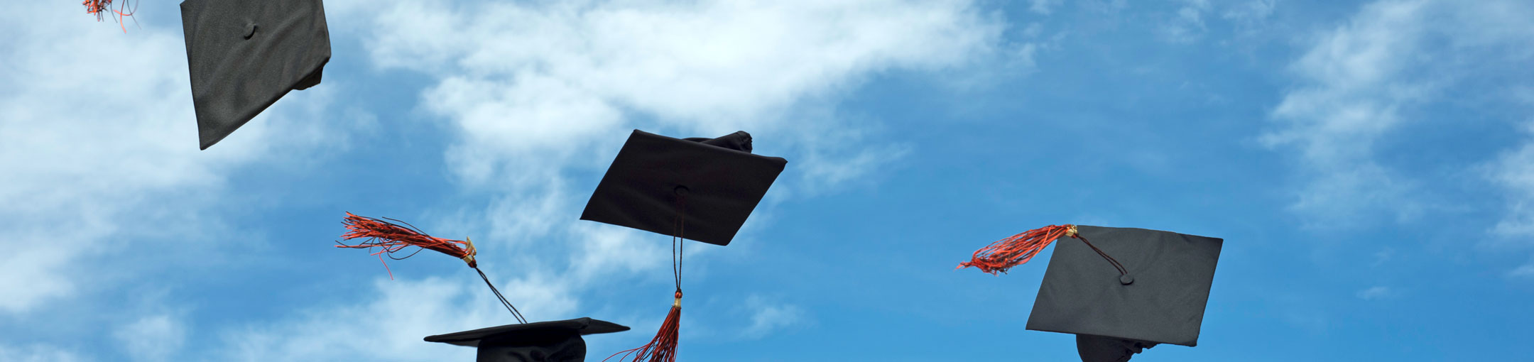 Graduation caps thrown in the air against a blue sky