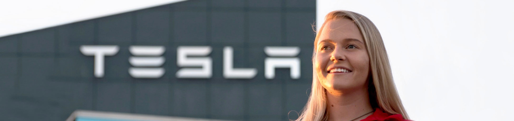 A female RIT student on co-op standing in front of a Tesla building.