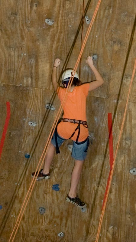Rock climber climbing up an indoor course