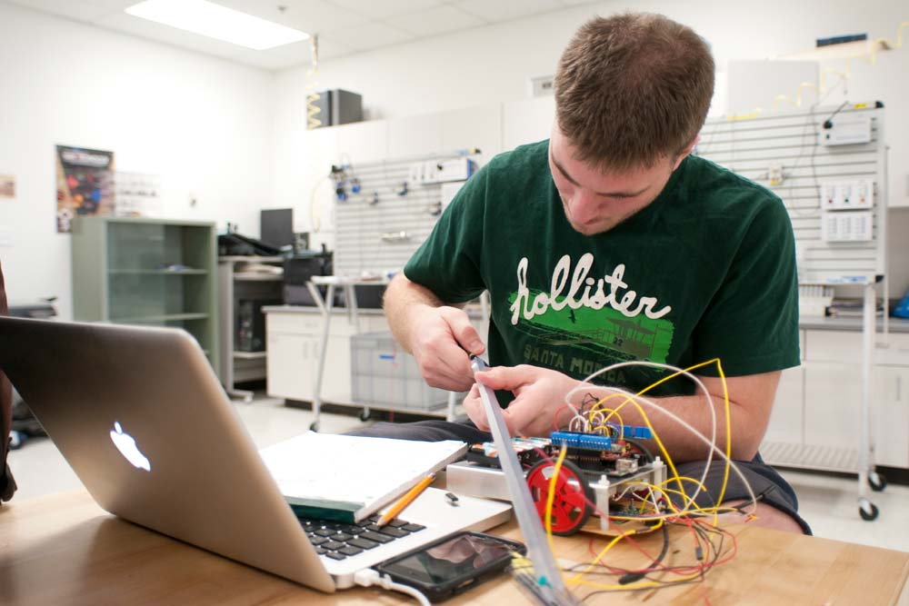 Student building an electronic gadget