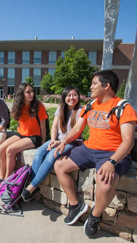 Students in orange RIT shirts sitting on a bench outside