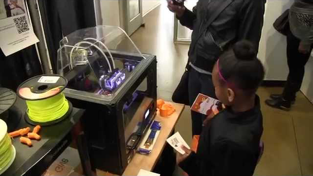 Young girl watching a 3D printer print out a prosthetic device.