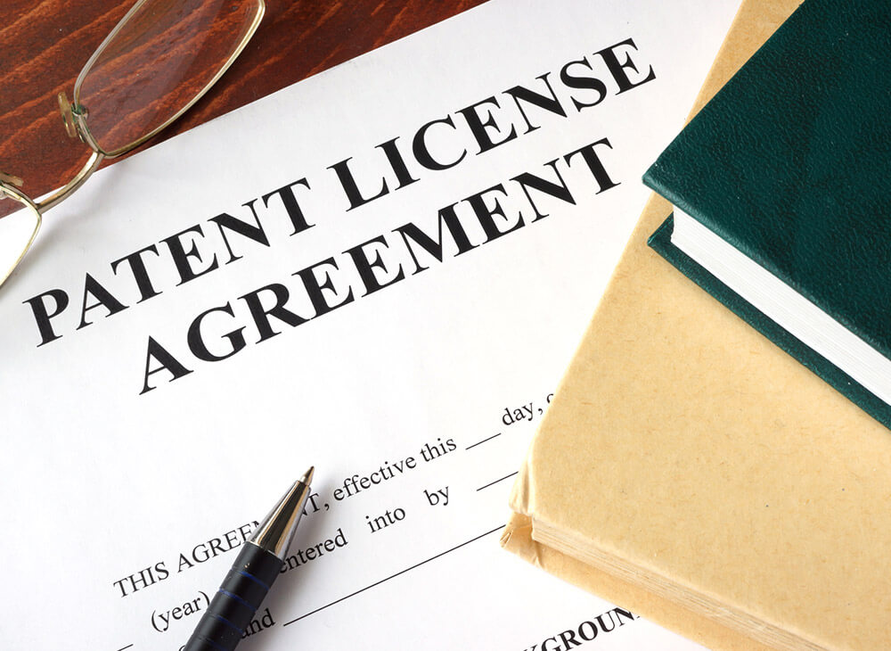 A patent license agreement with a pen and glasses placed on top of it