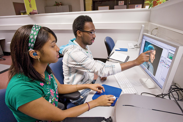 Two students, one with a visible hearing aid, work at a computer.