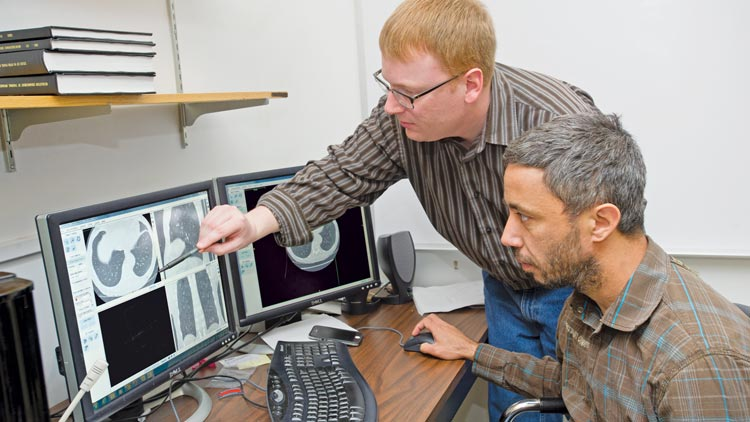 Nathan Cahill, standing, along with imaging science doctoral student Kfir Ben Zikri, is developing algorithms for a longitudinal study of lung nodules in CT scans.