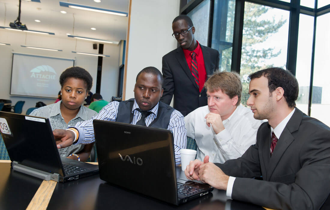 5 people dressed in business attire around 2 laptops