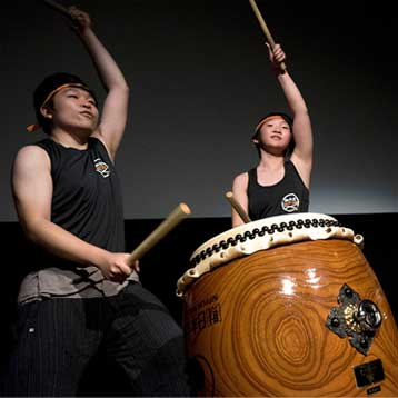 Two drum players hitting the same drum