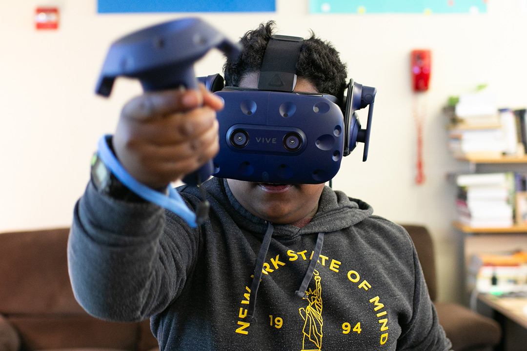 Student wears virtual reality goggles.