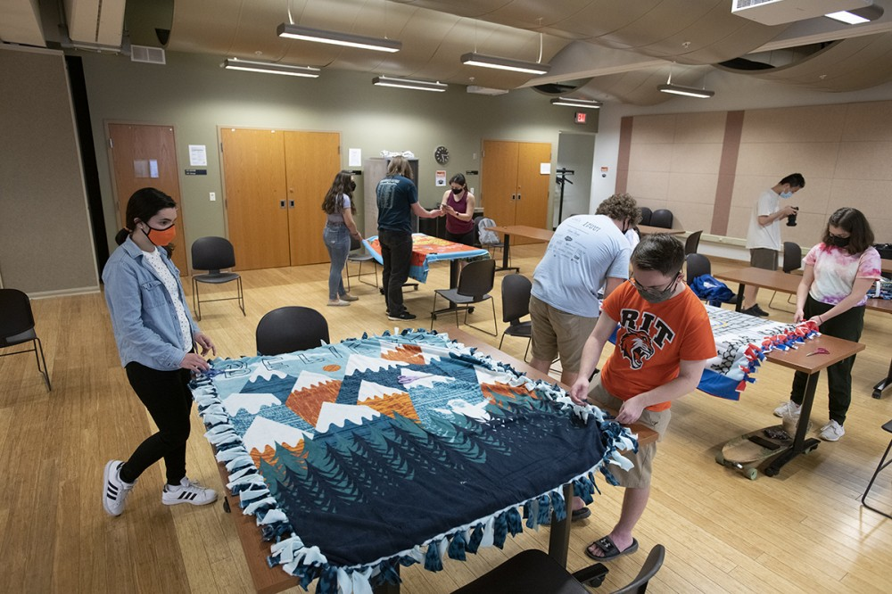 Photo by A. Sue Weisler <br> <p>RIT students from Circle K International make no-sew fleece blankets during Service Week on campus.</p>