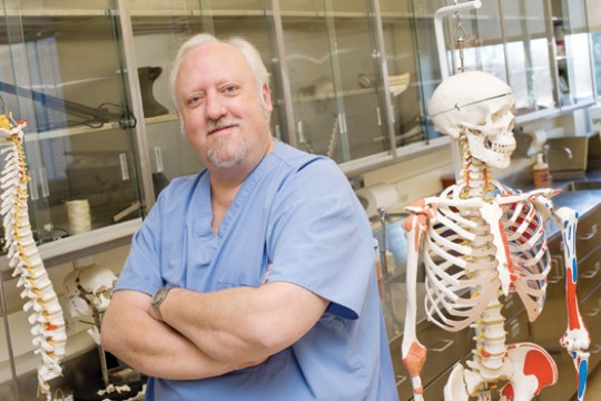 Jim Perkins poses for a photo next to a model of the full human skeleton and a model of the human spine.