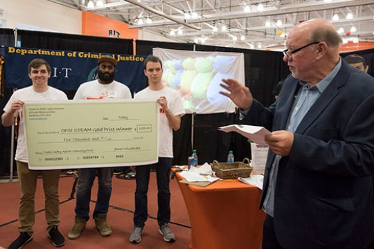 Three Clockwyse team members hold up a large check while the CPSI director talks to a crowd about their first-prize accomplishment.