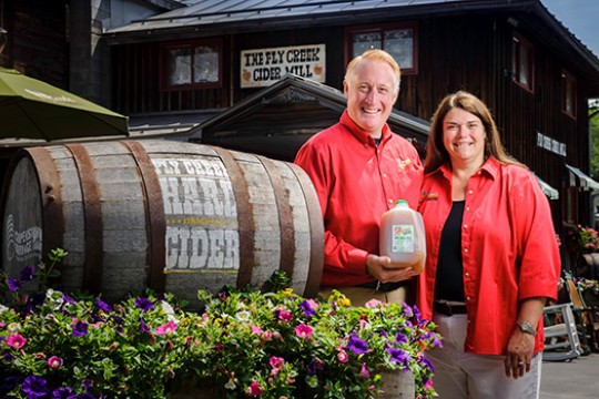 Bill and Brenda Michaels pose next to the entrance of their Cider Mill, holding a jug of their cider.