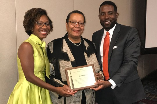 Three people pose for a photo holding dt ogilvie's, center, plaque she received for the Trailblazer Award.