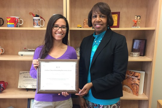 Triana Almeyda holds her Ph.D. Dissertation Award and poses for a photo next to Twyla Cummings.