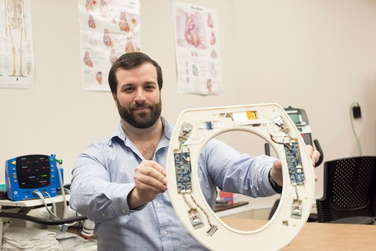 Researcher holds toilet seat with sensors attached to it.