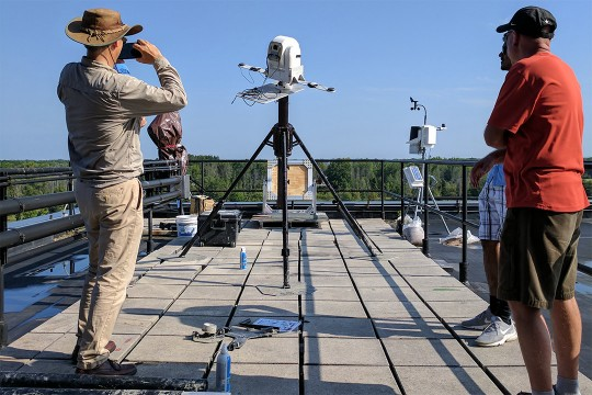 Three researcher watch hyperspectral camera on roof.