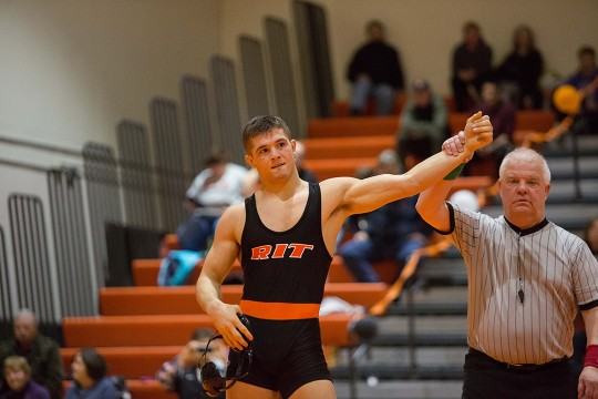 Student in wrestling singlet stand with ref raising his arm in the air