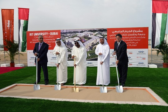 Five officials stick ceremonial shovels into a length of sand in Dubai