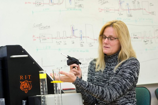 Researcher holds device that measure cigarette smoke