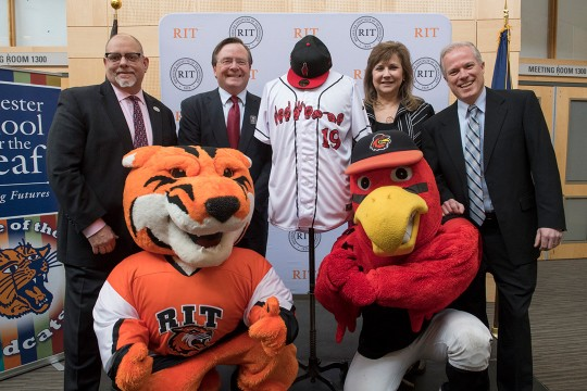 Four people pose with Tiger mascot and cardinal mascot
