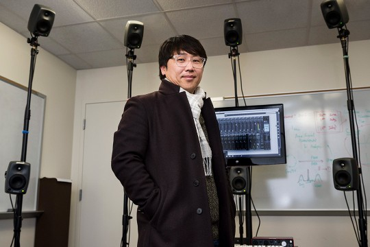 Researcher stands in front of TV screen surrounded by small speakers