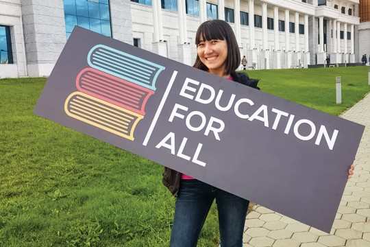 Woman holds sign that reads: Education For All.