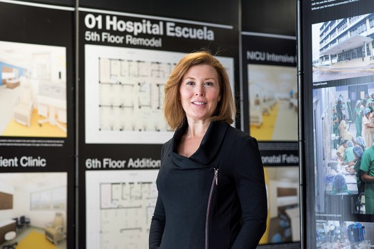 Woman stands in front of display of hospital floor plans