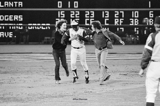 Hank Aaron rounds second base as two fans run beside him in 1974.