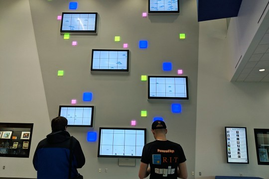 Two students play video game on six TVs mounted to wall.