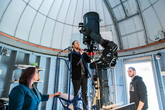 Students work on a telescope.